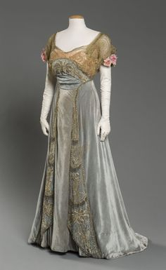"1912 Evening dress of light aqua silk velvet with peach silk satin, metallic lace and beadwork characterizes the end of La Belle Epoque, the ""beautiful era"" during which the arts flourished."