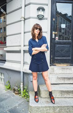 Irina Lakicevic of A Portable Package wears a button-down top, button-front skirt, socks, and loafers