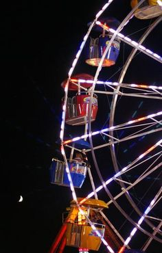 """Riders on the """"Euro Expo"""" get a good look at the moon rising over the fairgrounds. Greg Derr/The Patriot Ledger"""