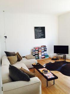 Helles, freundliches Wohnzimmer mit Bücherstapel, Flachbildfernseher und gemütlicher Atmosphäre. Wohnung in Stuttgart.