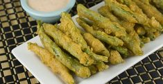 Fried Green Beans - Fresh green beans coated with a light beer battered and deep fried golden brown. Perfects served with a spicy Sriracha dipping sauce!