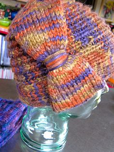 A pretty cloche style hat with a turned back brim trimmed with a large bow in verticle placement over the right ear and side seam. This hat was inspired by the cloche hats worn by the women in Edward Hoppers paintings. The style looks more like a felted sculptured and shaped hat when worn than a knitted cap. However, it has the advantage of being able to be folded in half and stored flat so it would be ideal for travel and packing. It has a definite vintage 1920's - 1930's feel. It is thick…