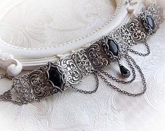 Ornate necklace/choker Symphony of depth by Midnight Vision Jewelry  This necklace/choker was made of an indigo blue Czech crystal jewel in antique silver frame, decorated by ornaments with antiqued finish. These lovely victorian ornaments are rich in details. Under the stone is hanging a matching faceted teardrop. The chain is decorated with little faceted beads. It can be worn close to the neck or a bit lower thanks to 2 extending chain.  Please choose the length of the chain for a…