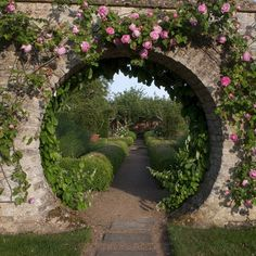 A rose covered circular opening to a path in the garden!!! Bebe'!!! Notice how the circular entrance draws the eye inward to the garden beyond!!!