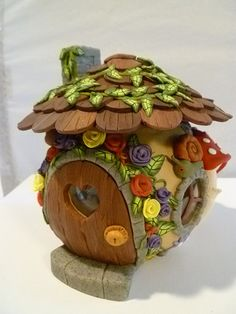 This delightful fairy house does double duty - both as a collectible and as a tea light candle holder. It has a clear glass vase inside which has been covered with polymer clay, and a polymer clay top for a roof has been added. This cute little forest house is embellished with roses, wildflowers, leaves, mushrooms, and tiny wildlife. The roof looks like primitive wood shingles and the chimney is stone colored clay as well as the trims for the door and windows. There are 3 round windows for…
