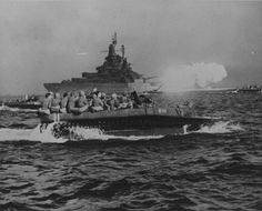 "USS Tennessee bombards Okinawa with her 14""/50 main battery, as LVTs carry troops to the invasion beaches. 1 April 1945."