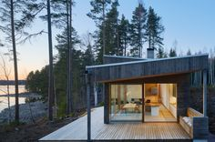 Dive Architects designed this stunner of a house on a lake. There is a Scandinavian feel with this house. All of the Alvar Aalto lighting caught my eye Dive Architects designed this stunner of a house Sweden House, Houses In Sweden, Roof Shapes, Haus Am See, Wooden Steps, Rural Retreats, Outdoor Seating Areas, Brick Fireplace, Architect Design