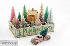 """Make any space merry and with holiday displays big and small! Meant to delight all ages, this vignette features a cabin nestled in a magical forest of colorful snow-dusted bottle-brush trees. To see more quick and easy holiday displays, check out the """"Quick Christmas Vignettes"""" article in the Holiday 2020 issue. Christmas Decorations, Christmas Ornaments, Holiday Decor, Christmas Trees, Magical Forest, Bottle Brush Trees, Vignettes, Farmhouse Style, Crates"""