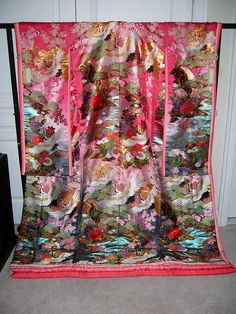Woven wedding kimono (uchikake) with a juni-hitoe layered effect on the sleeves and hem. The pink background is an unusual colour; most modern uchikake feature red, not pink. The design features cranes, streams, and flowers appropriate for both spring and autumn weddings.