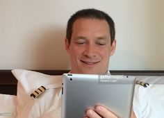 Pilot having a FaceTime conversation with his family from his hotel room on an iPad tablet.