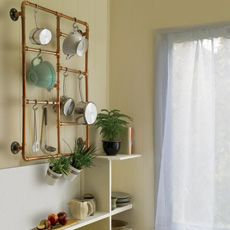 """How to Make a Pot Rack from Copper Pipe: bring a Victorian-era look into your kitchen with this tutorial by Jennifer Stimpson, for """"This Old House Magazine""""."""