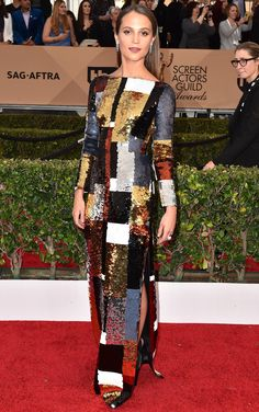 ALICIA VIKANDER wears a sleek sequin patchwork-print Louis Vuitton gown with shoes and high jewelry by the brand.