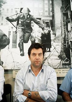 1986: Former East German border guard Conrad Schumann in front of the famous photo of him defecting to the West on August 15, 1961 aged 19. At that stage of construction, the Berlin Wall was only a low barbed wire fence. Schumann later moved to Bavaria but, suffering from depression, he hanged himself in 1998.