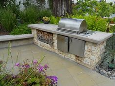 What an awesome outdoor grill area with wood storage for the firepit!