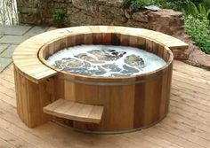 Outdoor round hot tub in wood on wood deck. Attractive for yard.