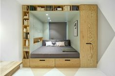 Das Schlafzimmer wird von einem Regal aus Holz umrahmt