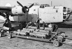 """Armourers at RAF St Eval manhandle 250 lb. depth charges from a bomb trolley as they prepare a Liberator GR Mark VA of 53 Squadron for a patrol. Moore's """"G-George"""" was loaded with 12 of the cylindrical weapons as well as a 600 lb. acoustic homing torpedo. Photo: Imperial War Museum"""