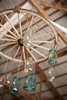 you won't have these wheel chandeliers - this is just to keep in mind the idea of using mason jars with tea lites for lighting hanging from tent frame or tree branches