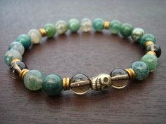 men's wisdom and prosperity mala bracelet made from moss agate, smoky quartz, and tibetan pyrite skull guru bead. this bracelet was made in honor of the acceptance of impermanence. the skull represent