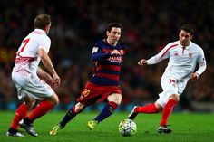 Lionel Messi of FC Barcelona runs with the ball under pressure from Michael Krohn-Dehli and Sebastian Cristoforo of Sevilla FC during the La Liga match between FC Barcelona and Sevilla FC at Camp Nou on February 28, 2016 in Barcelona