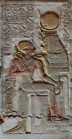 Egyptian hieroglyphic carving showing the goddess Isis - wearing the crown of Hathor - with the young Pharoah Seti on her lap. Wall of the temple of Abydos in Egypt