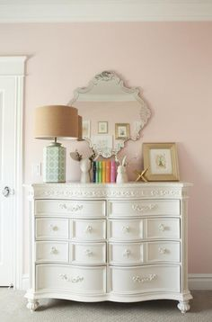 Draper Residence – Shop House of Jade, pink wall paint, white dresser, silver mirror, gold accents, gold frame, color coded books