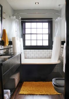 lovely b/w tub and subway tiling w/ dark wood details as in kitchen... lovely small space bathroom.
