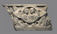 Marble relief, Roman.   This incomplete relief probably belongs to the front of a sarcophagus, although it could instead be the cover of a rectangular burial niche cut out of the rock (so-called loculus). Held up by male sea creatures emerging from the sea (tritones), the medallion contains the portraits of a deceased man and woman.