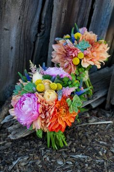 Colorful vintage inspired bridal bouquet using a variety of flowers in a palette of pink, orange, yellow, blue and green