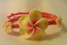 This handmade bracelet is made from dyed orange hemp, with one large and two small polymer plumeria beads and yellow E beads. It has an