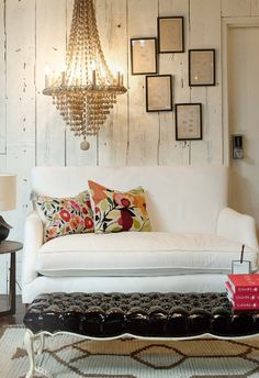 Love the mix if the white washed wood paneling, the crisp white couch, the bright floral pillows, and the black tufted ottoman.
