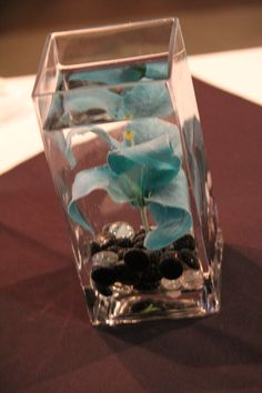 Dollar store vase, rocks, and flower. Just add water for a cute center piece for a wedding or party!