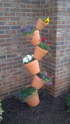did this in one of my flower beds Looks So COOL!!!!  Its a rebar stake driven into the ground, then you just stack the pots on top of each other(the pots have holes in the bottoms).