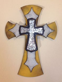 """Small wooden, triple layer, wall cross. Painted with yellow and silver acrylic paint and distressed with black spray paint. The piece is then topped with a small cross featuring a silver glass mosaic. Dimensions are approximately 8"""" x 11"""". Each cross is handmade with love and truly one of a kind."""