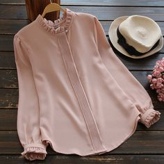 Love or want to try a preppy style that embraces more feminine features? Here is a blouse with classic designs including ruffled neckline and ruffles at the sleeve ends, pleats covering up the button-