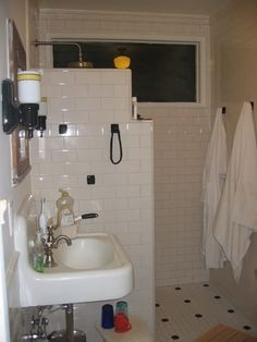 Doorless shower in a small space- key is an overhead shower that sprays directly down. Totally want to do this. I love that the towels can be hung right there.
