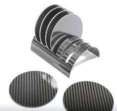 """This complete set of six (6) real Carbon Fiber coasters comes with a matching real carbon fiber tabletop stand. Made of solid carbon fiber, these spectacular carbon fiber discs are 4"""" wide and approxi"""