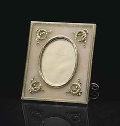 A SILVER-GILT AND AVENTURINE QUARTZ PHOTOGRAPH FRAME BY FABERGÉ, WORKMASTER MICHAEL PERCHIN, ST. PETERSBURG, CIRCA 1890. Rectangular, the quartz panel centering an oval aperture within a dot-and-dash border, the corners applied with ribbon-tied laurel wreaths, all within a key pattern border.