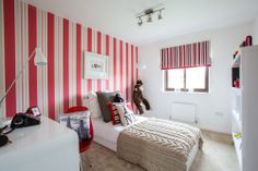 Boy's bedroom has an eye-catching red striped wall