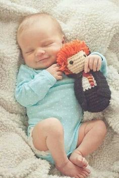 Baby with a knitted Ron Weasley doll.
