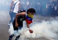 A demonstrator picks up a tear gas canister during clashes with security forces at an opposition rally in Caracas, Venezuela, April 6, 2017. REUTERS/Carlos Garcia Rawlins