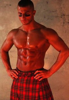 Hunky buffed tanned male wearing red plaid kilt