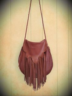 Premium rich tobacco colored cowhide leather bag hand-stitched with fringe detailing on the flap. Hand-braided leather strap with tassel ends. Small inside pocket. This bag is not lined.