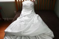 "Beautiful slimming strapless white wedding dress from David's Bridal. Style is a Satin A-line gown with bodice insert and corset laced back with privacy panel. Size is 16W (real dress size 12-14). Bustle professionally added to hold up the train of the dress. Bride was 5'8"" with 3"" heels. This dress was used for less than 3 hours and is slightly dirty on the bottom edges from an outdoor wedding."