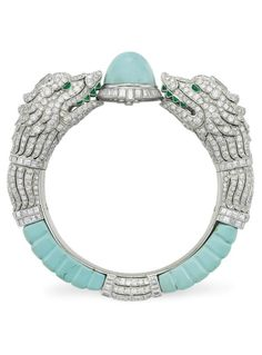 AN ART DECO DIAMOND, TURQUOISE AND EMERALD BANGLE BRACELET, CIRCA 1935. Designed as two circular and single-cut diamond opposing baroque dolphin heads, with baguette-cut diamond accents and calibré-cut emerald eyes and teeth, holding a turquoise cabochon within a baguette-cut diamond surround, to the ribbed turquoise, old and single-cut diamond surround, with French assay marks for platinum and 18k gold. With obscured jeweler's marks and numbered. #ArtDeco #bangle