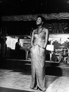 Sarah Vaughan smiles on stage with her hands in her gown pockets, c. 1944.