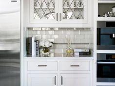 Glass-Front Cabinets Above Subway Tile Backsplash in Kitchen Nook