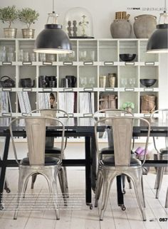 Love this - my dream casual dining room must feature tolix chairs, tiny topiariesand a wall of charming cubbies filled with heavy glassware.