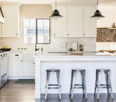 Cottage kitchen with white shaker cabinets with oil-rubbed bronze hardware and white marble counters alongside a beveled subway tile backsplash.