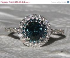 A beautiful and unique engagement ring featuring a round teal blue sapphire and blue diamonds in white gold diamond double halo.    The center